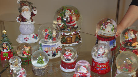 Hand decorating many Christmas snow globe balls on a table Footage