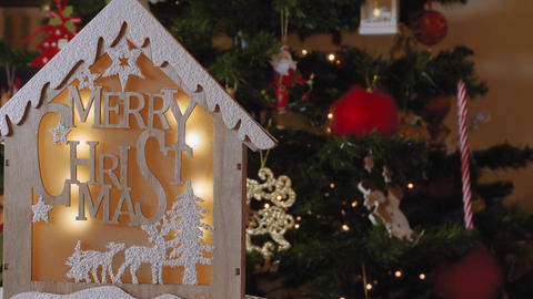Wooden crib design with Merry Christmas message before lit tree Footage