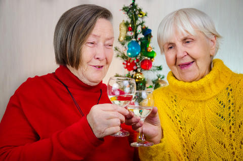 two old grandmothers in new year midnight clinking glasses. senior lady take Photo