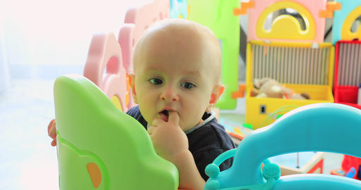 Adorable Baby Boy Standing In Colorful Playpen Footage