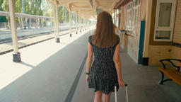 BackView of Woman in Black Dress Walking with Black Suitcase along Train Station Footage