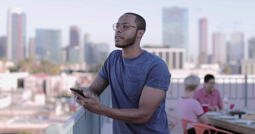 Young adult male messaging friend from a rooftop party ビデオ