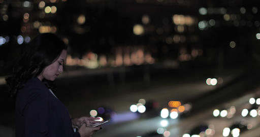Young adult female taking photo with smartphone of city skyline at night Footage