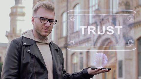 Smart young man with glasses shows a conceptual hologram Trust Footage
