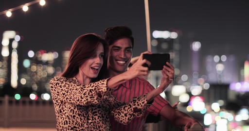 Young adult couple taking selfie with city skyline at night ビデオ