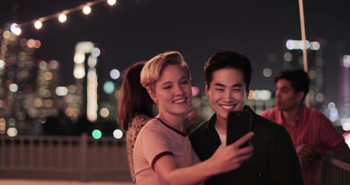 Young adult couple taking selfie with city skyline at night Footage