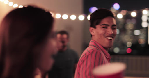 Young adult couple looking at city skyline at a party Footage