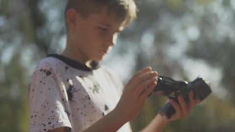 Child holds a cars remote control and toy car. Boy with a... Stock Video Footage