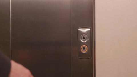 Business man pushing button for calling elevator and coming into lift GIF