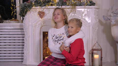 Smiling sister hugging little brother on Christmas fireplace background GIF
