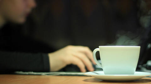 girl with tea cup plays laptop Stock Video Footage