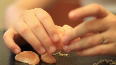 girl cleans tangerine and smiles Stock Video Footage