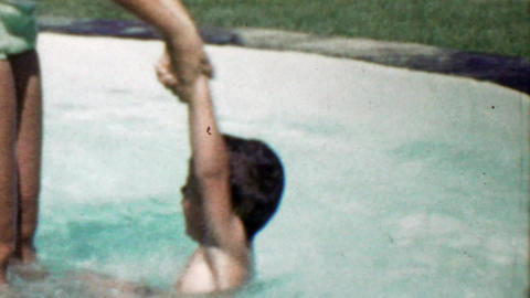 1963: Mom helping son shallow kiddie splash play swimming pool Footage