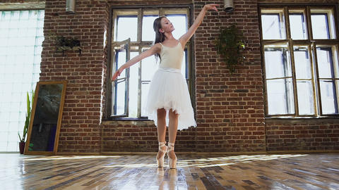 Young ballerina in white tutu and ballet shoes is practicing dance moves. Young Footage