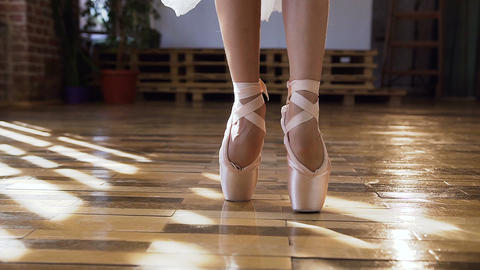 Close-up of ballerina graceful feet in ballet shoes dancing ballet elements on Live Action