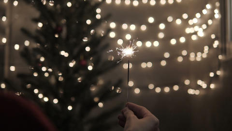 Sparkler in hand with celebrate Christmas lights background Stock Video Footage