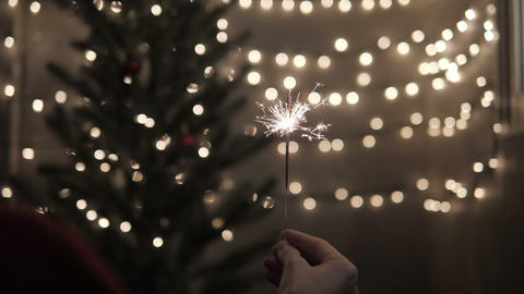 Sparkler in hand with celebrate Christmas lights background Footage