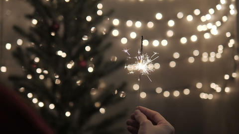 Female holding sparkler with Christmas tree lights at party Live Action