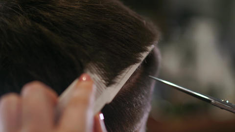 Close-up, master hairdresser does hairstyle and style with scissors and comb Footage