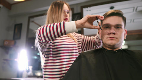 Interior shot of working process in modern barbershop. Side view portrait of Footage