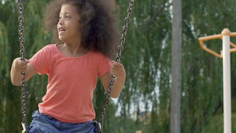 Cute black girl having fun, swinging up and down in yard, carefree childhood Footage