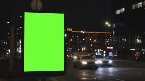 Billboard with a green screen, located on a busy street. Cars move in the GIF