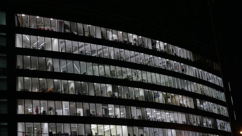 Large office building in the evening. Lighted windows. People finish the job Footage