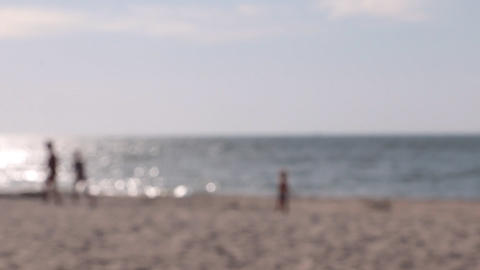 Child playing on the beach. Blurred Footage