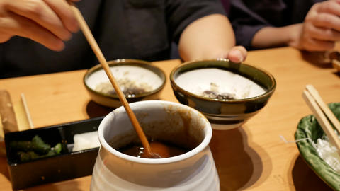 Motion of woman pouring sauce on sesame at Japanese restaurant with 4k Live Action