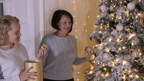 Daughter and mother decorating Christmas tree Live Action