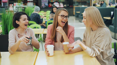 Happy young people are talking and laughing in cafe then clinking glasses Footage