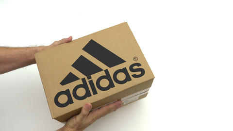 ADIDAS logo on the carton in hands. Editorial clip ビデオ