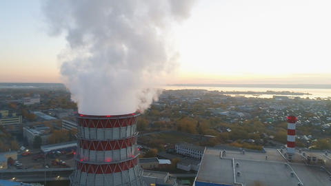 aerial cooling tower with steam cloud against city near lake Footage