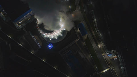 upper view brightly lit cooling tower with steam pillar Live Action
