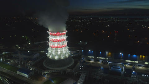 aerial panorama cooling tower against dark city in dusk Live Action