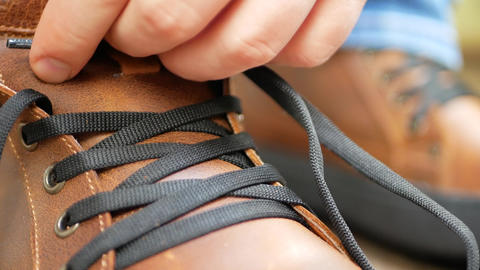 Man tying the laces on leather shoes boot Live Action