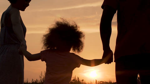 Silhouettes of parents having fun with their little daughter against sunset Footage
