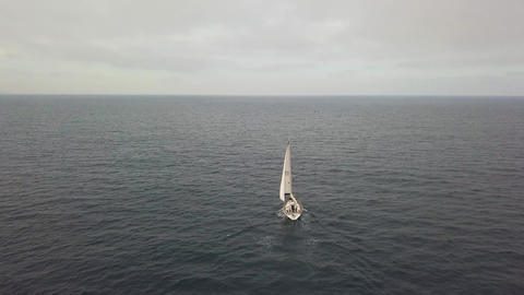 Aerial view luxury sail boat sailing in blue sea on cloudy sky on horizon Footage
