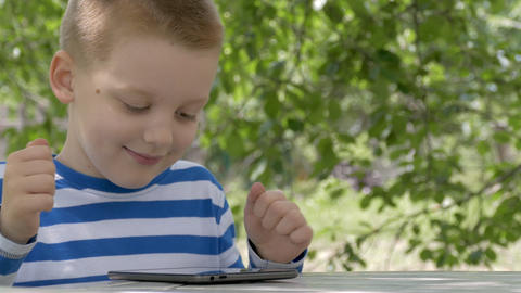 Cute Little Boy Using A Tablet And Wins A Game Footage