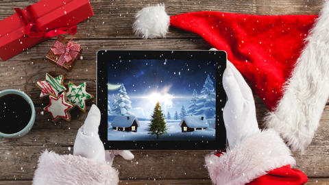 Video composition with snow over of top view of santa holding tablet Live Action