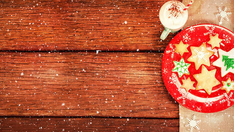 Christmas cookies and hot drink on wood combined with falling snow Animation