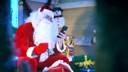 Santa Claus reading messages on smartphone Live Action