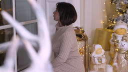Beautiful adult woman sitting near window at Christmas eve in cozy living room GIF