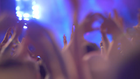 A slow motion of a crowd clapping hands at a concert show GIF