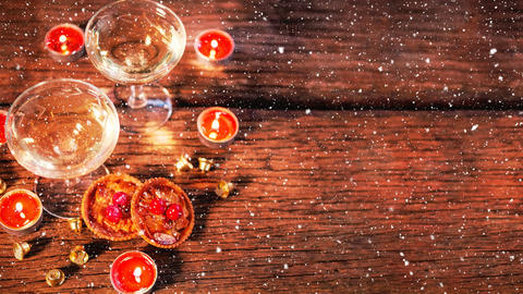 Candles and two glasses on wood combined with falling snow Animation