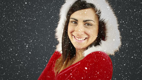 Video composition with falling snow over smiling girl in santa suit while turning Animation
