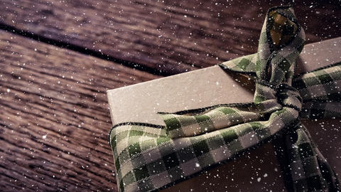 Falling snow with Christmas gift on wood Animation