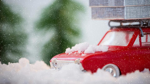Red model car in winter scenery combined with falling snow Live Action