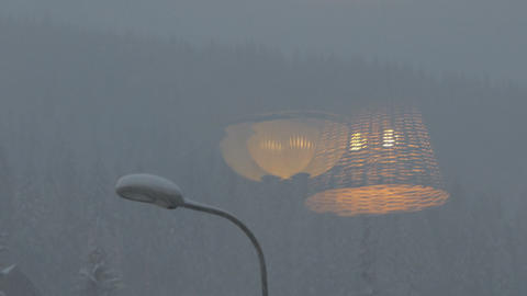 Snowfall on the mountains - reflection of lamp on the window GIF