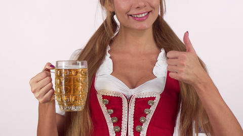 Gorgeous Oktoberfest woman in sexy dirndl dress holding beer showing thumbs up Live Action